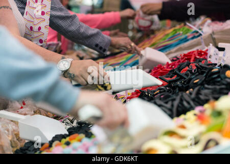 Members of the public help themselves to liquorice sweets, at the Pontefract Liquorice Festival, in Pontefract. - Stock Photo