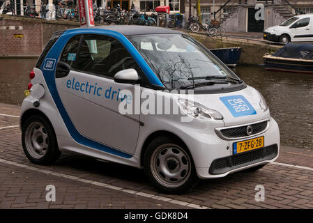 An electric car being charged in Amsterdam, Holland, Netherlands. - Stock Photo