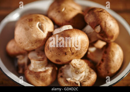 A bowl of raw crimini mushrooms - Stock Photo