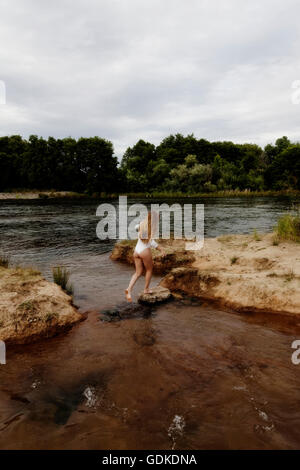 Attractive Caucasian Teen Girl Crossing From Island To Island In River Wearing White Leotards From Back - Stock Photo