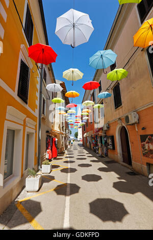 Open umbrellas hanging from strings in the street of Novigrad - Stock Photo