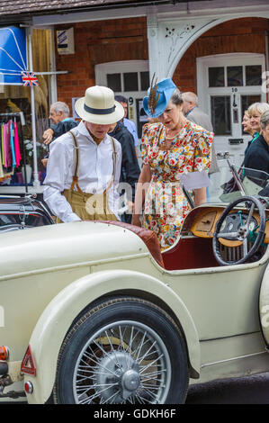 Woodhall Spa 1940s Festival - couple dressed in 1940s outfits at a sports car of that period - Stock Photo