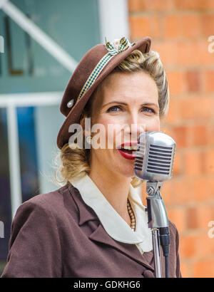 Woodhall Spa 1940s Festival - Woman in traditional 1940s dress singing - Stock Photo