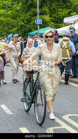 Woodhall Spa 1940s Festival - Woman in traditional 1940s dress with bicycle - Stock Photo