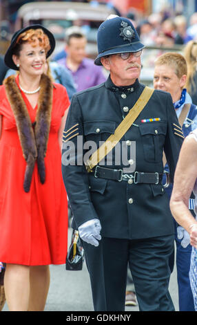 Woodhall Spa 1940s Festival - woman dressed in 1940s style with fox fur and hat and policeman - Stock Photo
