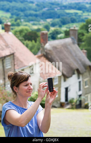 Woman talking a selfie by famous cottages at Gold Hill, Shaftesbury, Dorset in July - Stock Photo