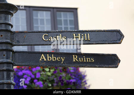 Signpost showing direction to Castle Hill and Abbey Ruins at Shaftesbury, Dorset in July - Stock Photo