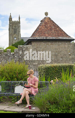 Young woman having lunch at Park Walk with Holy Trinity Church in the distance, Shaftesbury, Dorset in July - Stock Photo