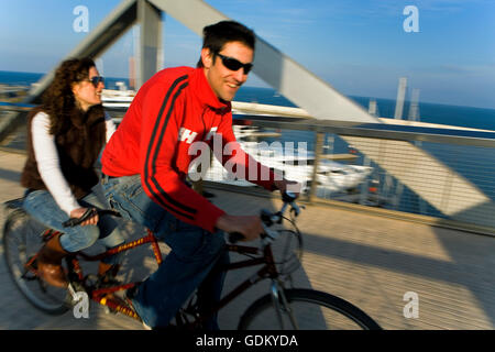 two friends riding tandem on bridge in Yacht club and marina, Forum Area, Barcelona, Spain - Stock Photo