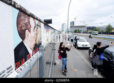 Tourists take photos in front of the painting 'Fraternal Kiss betwen Leonid Breschnew and Erich Honecker' (also - Stock Photo