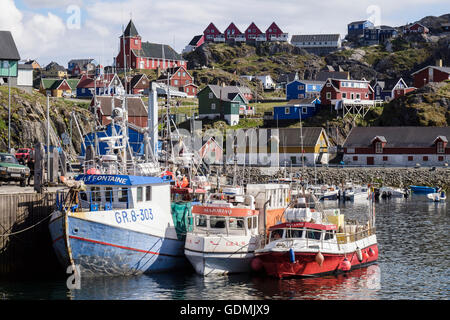 Greenlandic fishing boats moored in northernmost year-round ice-free arctic port with old town behind in summer. - Stock Photo