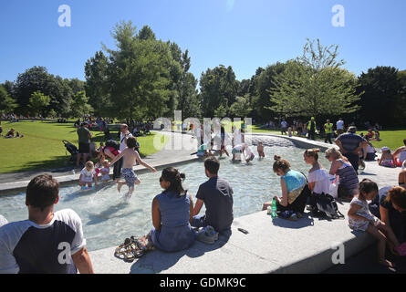 People enjoying the sunshine at the Diana, Princess of Wales Memorial Fountain in Hyde Park, London as a mini heatwave - Stock Photo