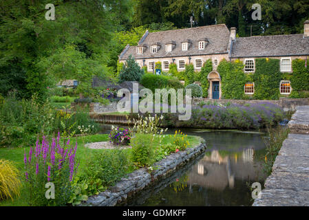 View of River Coln and Swan Hotel in the Cotswolds village of Bibury, Gloucestershire, England - Stock Photo
