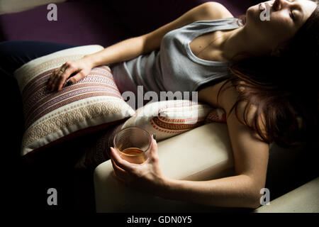 sad lonely woman drinks alcohol in the dark. Glass in sharp focus. female alcoholism - Stock Photo