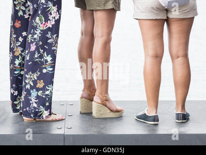 Three women wearing different types of footwear: heels and flats - Stock Photo