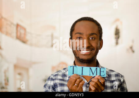 Headshot handsome man holding up small letters spelling the word time and smiling to camera - Stock Photo