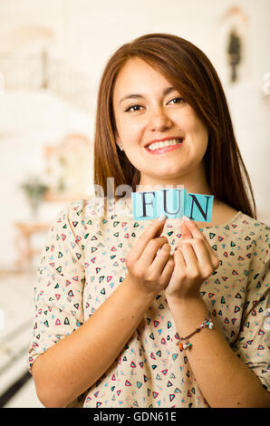Headshot charming brunette woman holding up small letters spelling the word fun and smiling to camera - Stock Photo