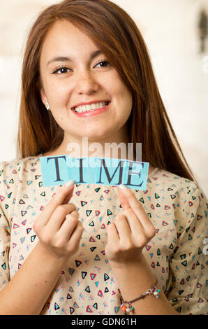 Headshot charming brunette woman holding up small letters spelling the word time and smiling to camera - Stock Photo