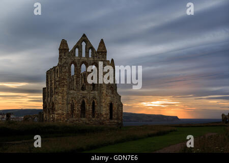 The ruins of Whitby Abbey against a sunset. In Whitby, North Yorkshire, England - Stock Photo