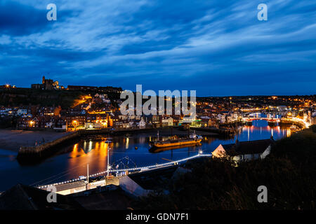 Whitby Abbey, with harbour in foreground, at night. In Whitby, North Yorkshire, England. On 16th July - Stock Photo