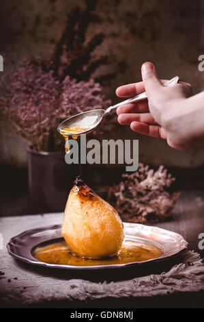 Poached pear with honey sauce - poire belle hellene in a rustic mood - Stock Photo