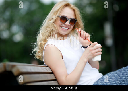 Attractive blonde in sunglasses with white-toothed smile - Stock Photo