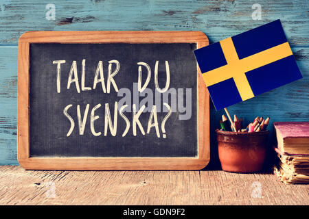 a chalkboard with the question talar du svenska?, do you speak Swedish? written in Swedish, a pot with pencils, - Stock Photo