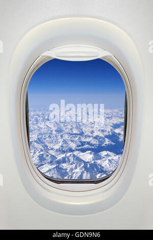 Window of an airplane from inside, view on snowy mountains (the Alps) - Stock Photo