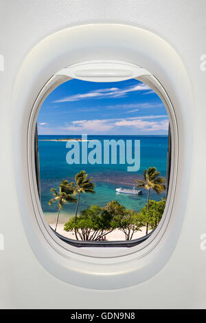 Window of an airplane from inside, view on a tropical beach and sea - Stock Photo