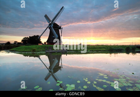 sunrise on Dutch farmland with windmill reflected in river - Stock Photo