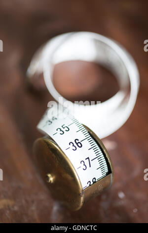 A partly unrolled reel of white tape measure displaying metric side and laid on a dark wooden surface - Stock Photo
