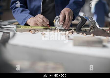 Hands of carpenter measuring wood on workshop bench - Stock Photo