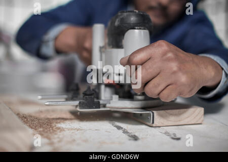 Close up of carpenter's hand using jigsaw tool in workshop - Stock Photo