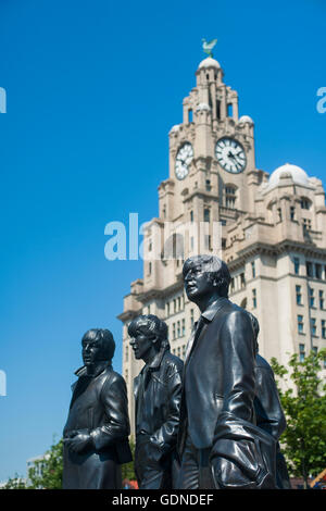 The Liverpool Liver buildings with the Beatles statues in the foreground - Stock Photo