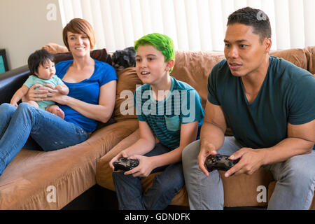 Mother with baby watching father and son playing video game on sofa - Stock Photo