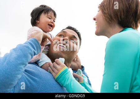 Couple playing piggyback ride with baby in park - Stock Photo