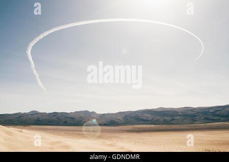 Desert landscape and semi circle vapour trail in blue sky, Olancha, California, USA - Stock Photo