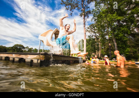 Man jumping from pier slide at Jackson Lake, Georgia, USA - Stock Photo