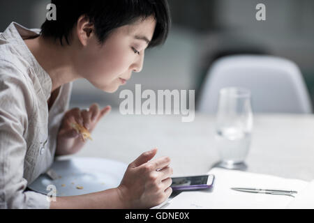 Woman using smartphone while eating - Stock Photo