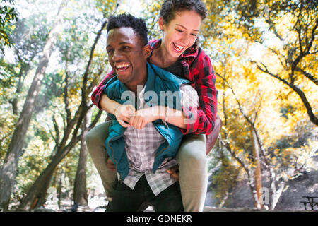 Young female hiker getting piggy back from boyfriend in forest, Arcadia, California, USA - Stock Photo