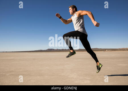 Male runner running on dry lake bed, El Mirage, California, USA - Stock Photo