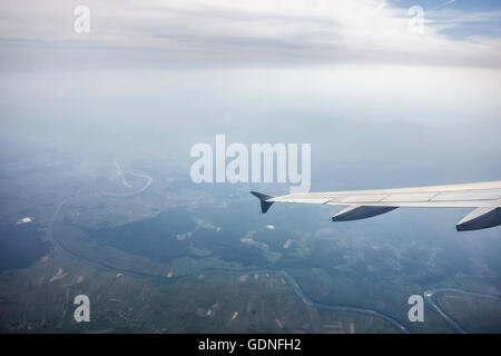 A view of the Earth relief with river and the cloudy sky from the airplane. - Stock Photo