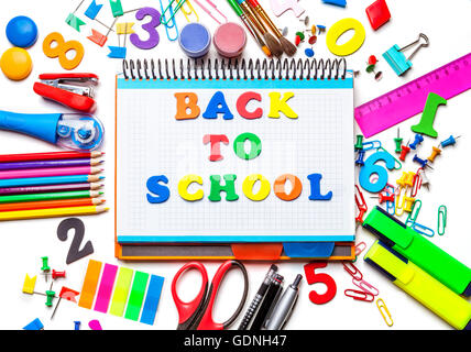 Various school supplies isolated on white background. Notebook in the center with the inscription of the letters - Stock Photo