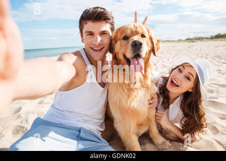 Young happy couple with dog taking a selfie at the beach - Stock Photo