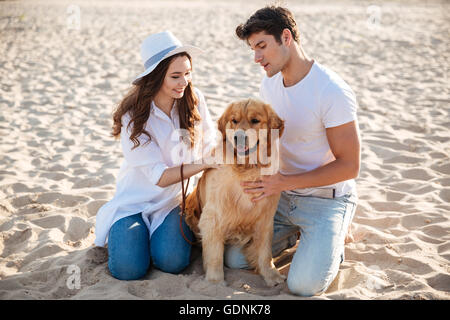 Beautiful young couple spending time on the beach with their dog - Stock Photo