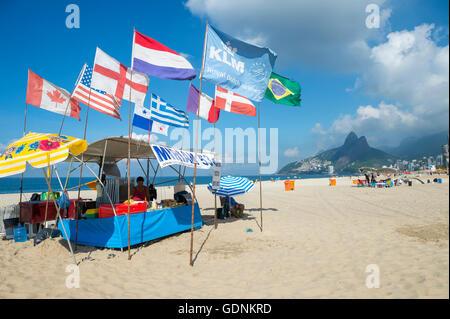 RIO DE JANEIRO - APRIL 4, 2016: International flags fly above a barraca (Brazilian beach shack) on Ipanema Beach. - Stock Photo