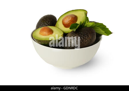 Fresh Healthy Whole and Halved Avocados Covered in Lemon Juice in White Round Bowl with Basil Leaves on Clean White - Stock Photo