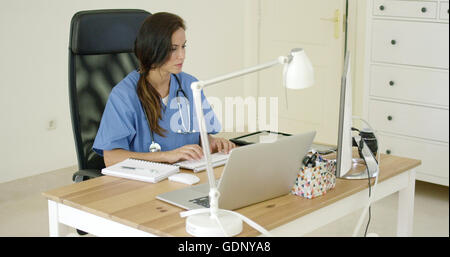 Young female doctor sitting typing in her office