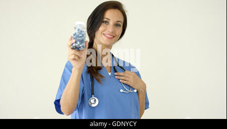 Young brown haired doctor in scrubs holds bottle - Stock Photo