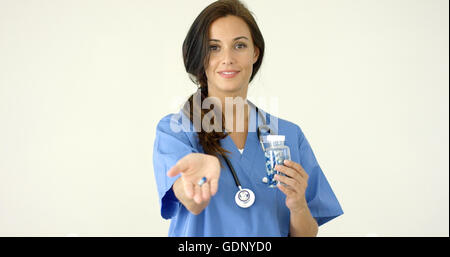 Attractive female doctor holding out a pill - Stock Photo
